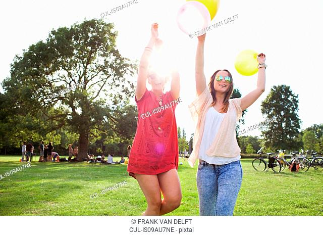 Two young women dancing with balloons at park party