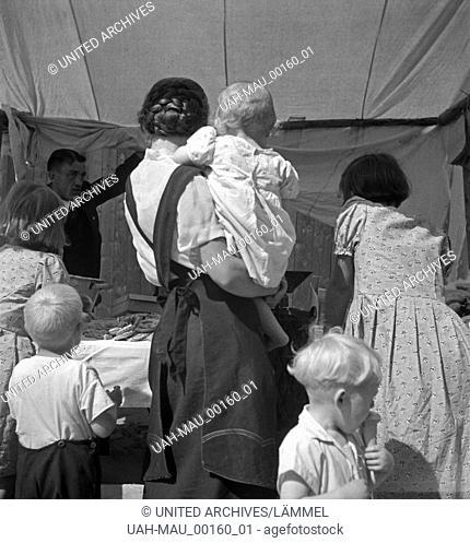 Eine Gruppe von Leuten drängt sich vor einem Marktstand am Markttag, Deutschland, 1930er Jahre. A group of people crwoding in front of a booth at a market
