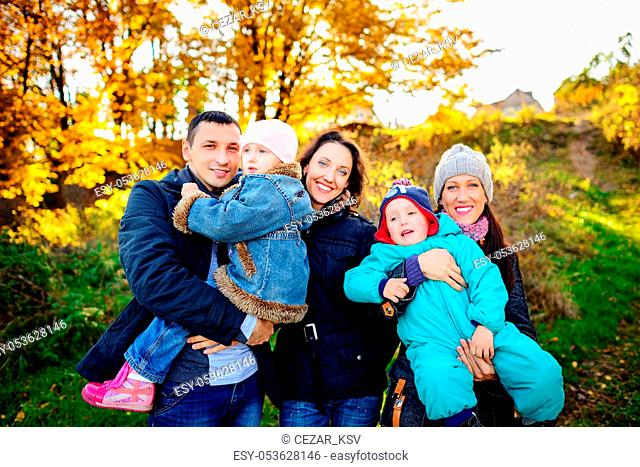 Young family, parents with small children in golden autumn