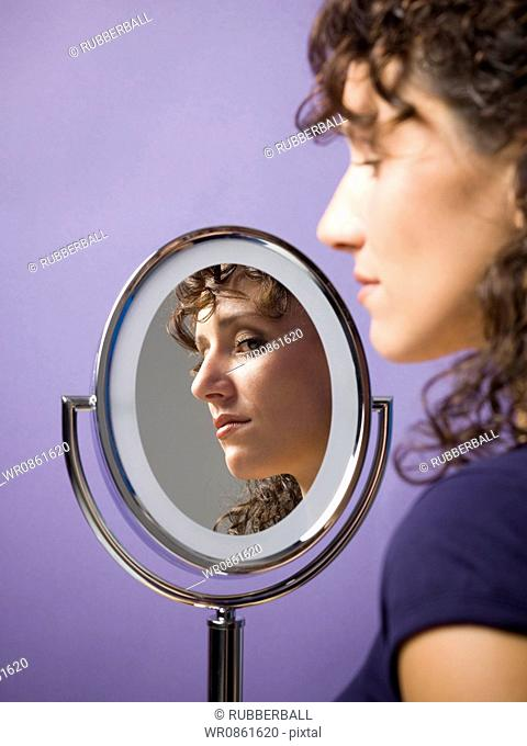 Close-up of a young woman looking into a mirror