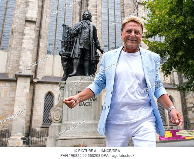 30 July 2019, Saxony, Leipzig: Hans-Jürgen Beyer stands in front of the Thomaskirche Leipzig at the Bach monument, where it all began