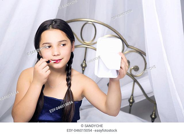 little girl sitting on a bed looks in the mirror and painting lips like her mom