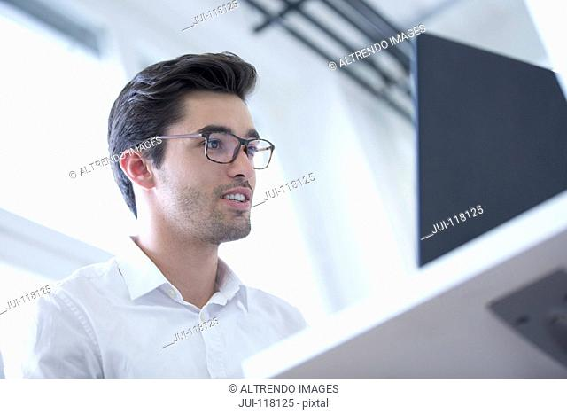 Businessman At Desk Using Laptop In Modern Office