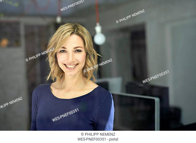 Portrait of blond woman behind window pane