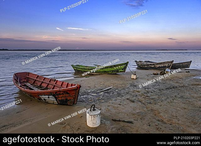 Wooden fishing boats on the shore / riverbank of the Paraná River / Río Paraná in the village Yahapé at sunset, Iberá NP, Corrientes, Argentina