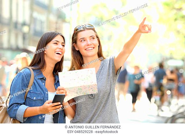 Two happy tourists sightseeing holding a map and pointing up in the street