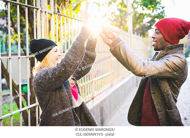Couple doing high five beside steel fence