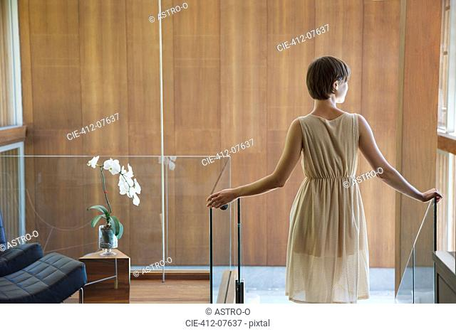 Woman standing at top of stairs in modern house