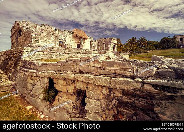Side view of the remains of a small Mayan temple in the Tulum complex in Mexico taken at sunset