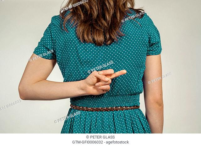 Young woman giving the finger behind her back