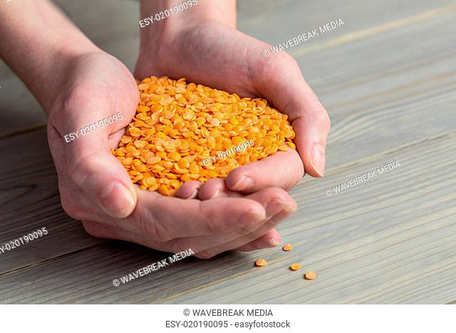 Woman showing handful of red lentils
