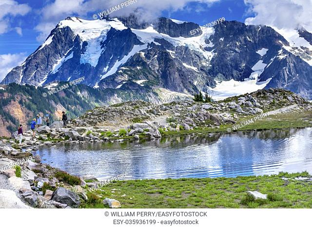 Hikers Mount Shuksan Pool Reflection Summer Artist Point Mount Baker Highway. Pacific Northwest, Washington State, Snow Mountain Grass Trees