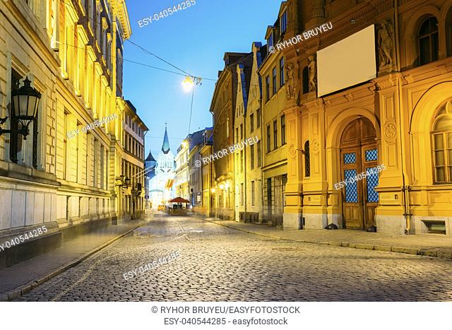 Riga, Latvia. Evening View Of Deserted Pils Street With Ancient Architecture In Bright Warm Yellow Illumination Under Summer Blue Sky