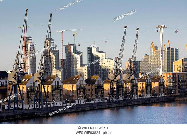 UK, London, Docklands, renovated residential buildings and harbor cranes, gondolas of the Emirates cable car