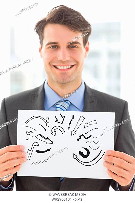 Grey arrow doodles on card held by business man smiling