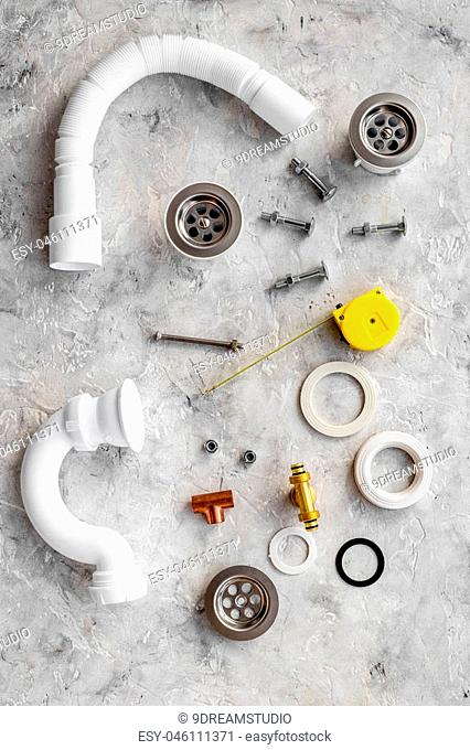 Disassembled sink drain pipe on grey stone background top view