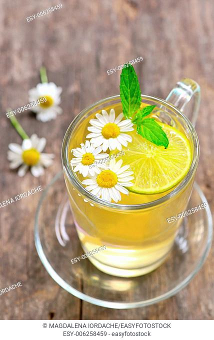Herbal tea with fresh chamomile flowers and lemon on wooden background