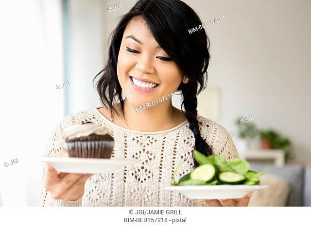 Pacific Islander woman choosing between cupcake and salad