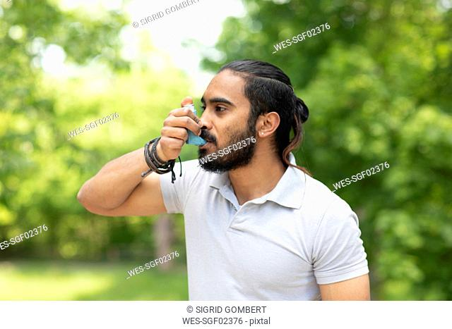 Young man in nature using asthma inhaler