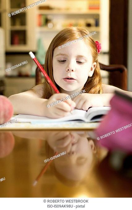 Girl doing school homework at dining room table