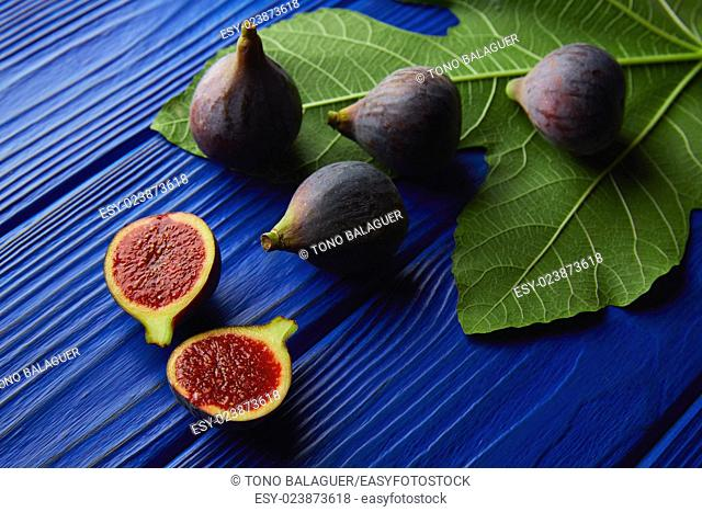 figs raw cutted fruits and fig tree leaves on blue wooden table