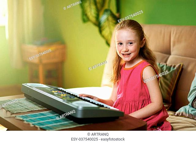 cheerful girl sits near an electronic piano