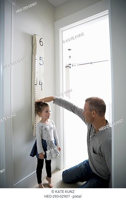 Father measuring daughter height