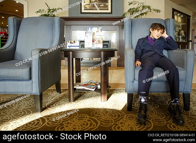 A small boy in a suit sits tiredly in a large chair in a hotel lobby