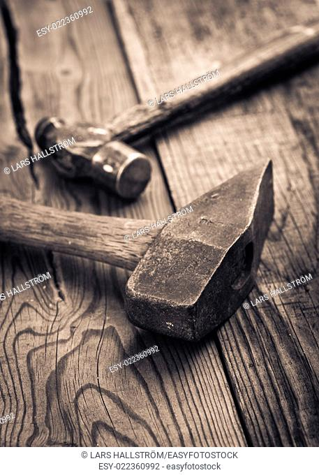 Vintage hammer lying on wooden surface of workbench. Conceptual image of home improvement, DIY and carpentry