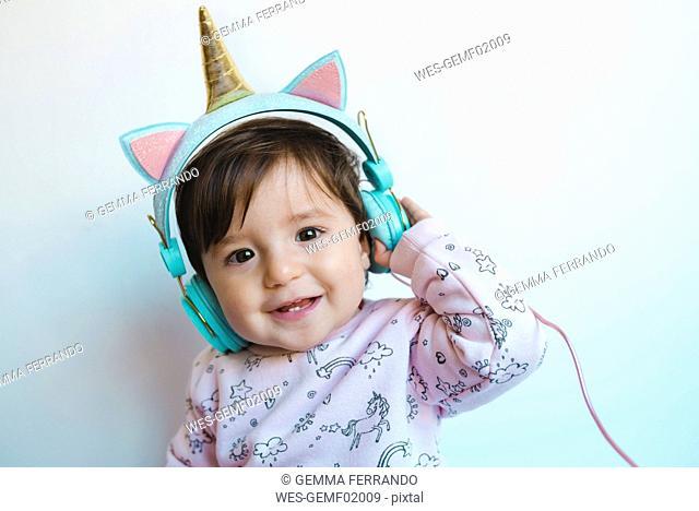 Portrait of smiling baby girl with unicorn headphones listening music