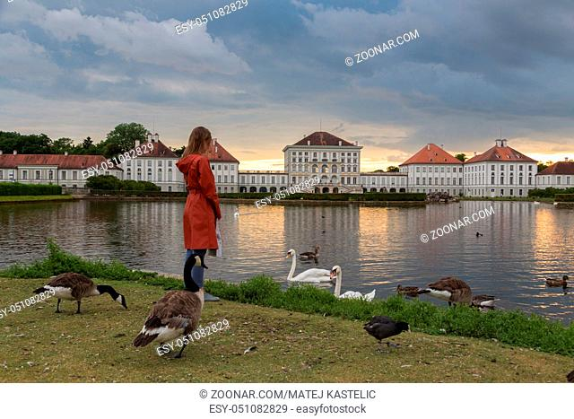 Dramatic scenery of Nymphenburg palace in Munich Germany. Sunset after the sorm. Woman feeding white swans and duks swimming in pond in front of the palace