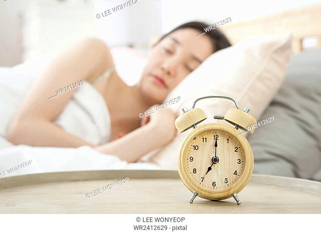 Portrait of young sleeping woman in bed with alarm clock