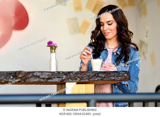 Young woman sitting indoor drinking coffee. Cool young modern caucasian female in her 20s. Cafe city lifestyle