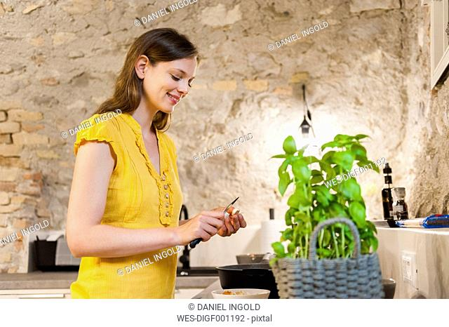 Woman in kitchen preparing spaghetti sauce