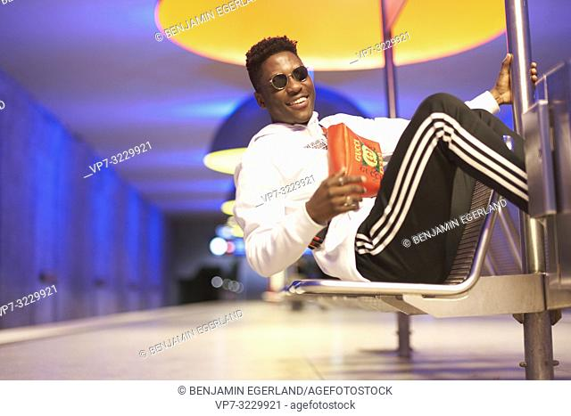 young man on bench in underground station, public transport, in Munich, Germany