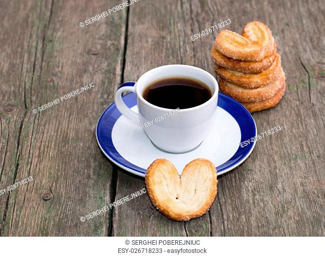 coffee on a saucer, and a column from cookies, on a wooden table, a subject food and drinks