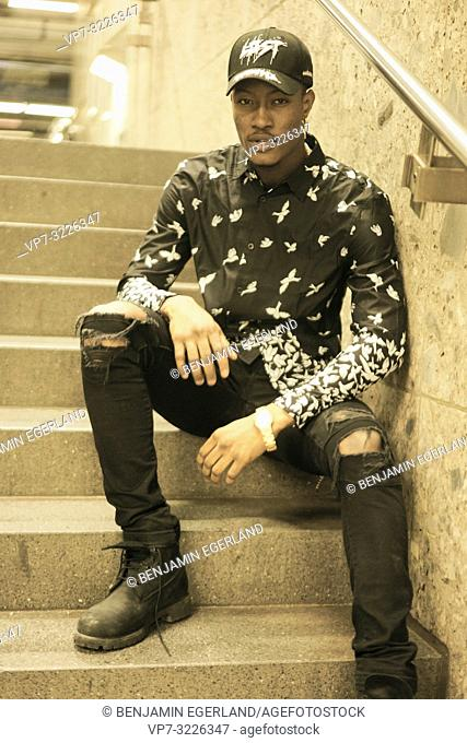 man sitting on stairs, casual fashion, in Munich, Germany