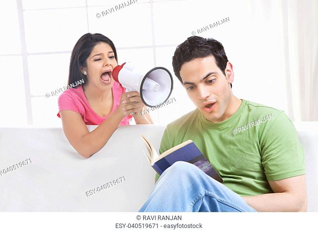 Young man reading while young woman is screaming into a megaphone