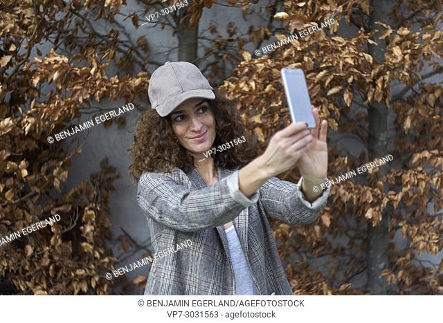 happy multi-cultural woman with cap taking selfie with smart phone, standing against autumn leaves. Fashion blogger Aslihan Kiratli