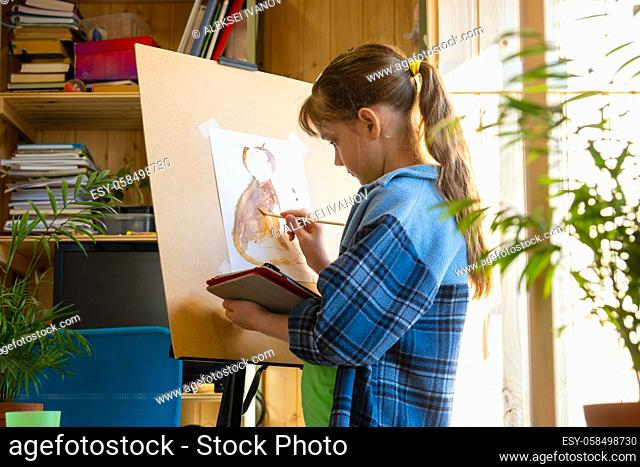 A ten-year-old girl draws with paints on an easel, holding a tablet computer in her hands