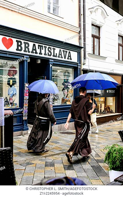 Monks carring umbrellas as they walk through the streets of Bratislava