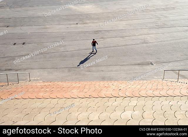 Young boy skateboarding in a city park in sunny day