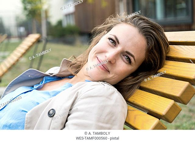 Portrait of happy blond woman relaxing on deck chair