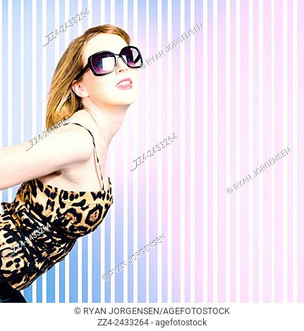 Trendy fashion model with short blond hair wearing eighties style leopard print outfit posing on striped purple background. Fashion lioness
