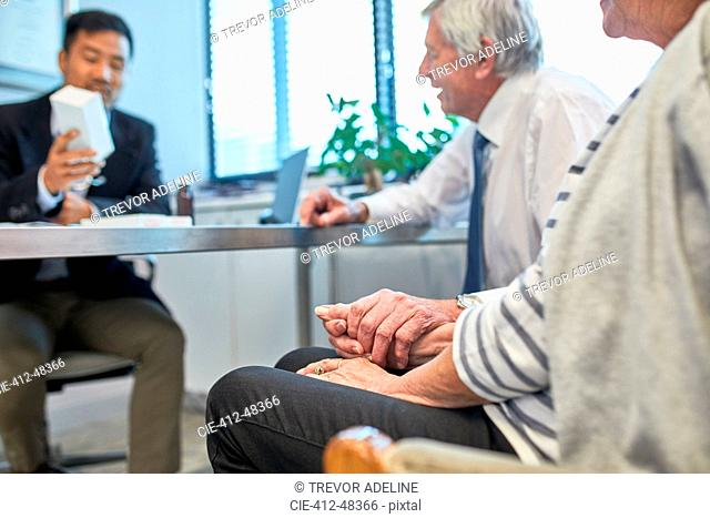 Doctor talking with senior couple in clinic doctors office