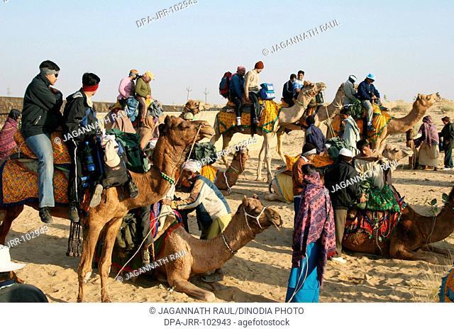 Camel ride at Sam Thar desert safari sand dunes , Jaisalmer , Rajasthan , India