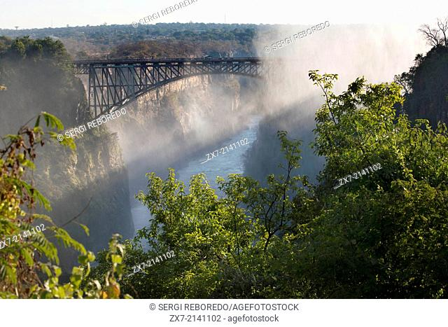 Views of Victoria Falls. Behind, the bridge between Zambia and Zimbabwe. For more than 50 years the bridge was crossed regularly by passenger trains as part of...