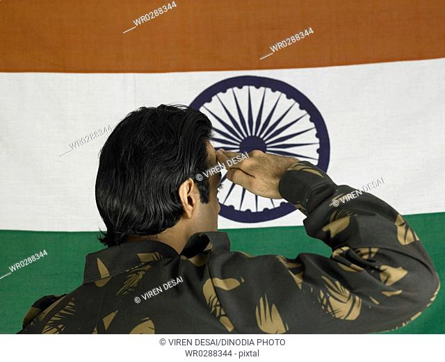 Indian army soldier saluting and looking at flag of India in background MR702A