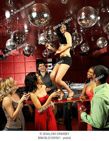 People watching woman dancing on bar in nightclub