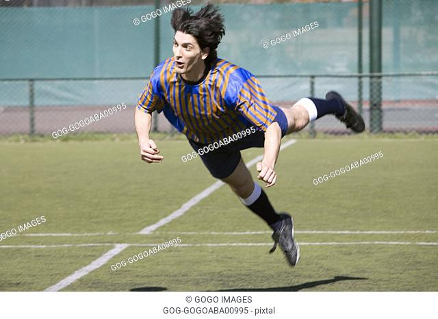 Soccer player jumping on the field